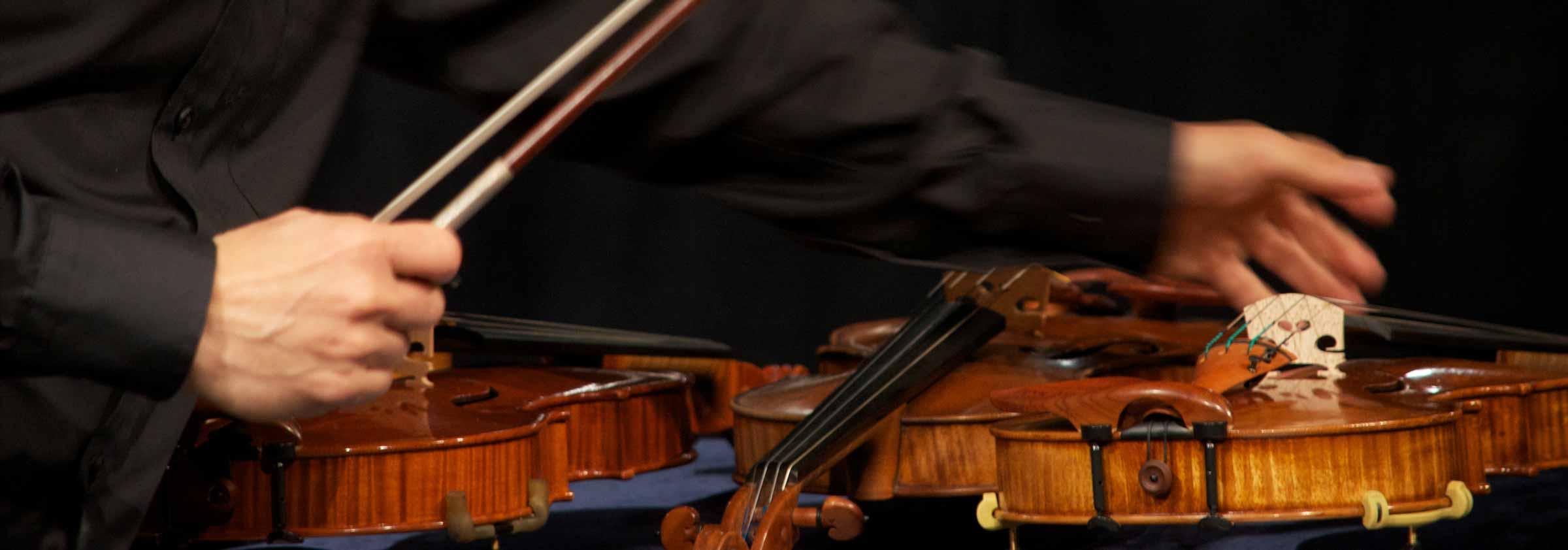 mann greift zu einer Geige